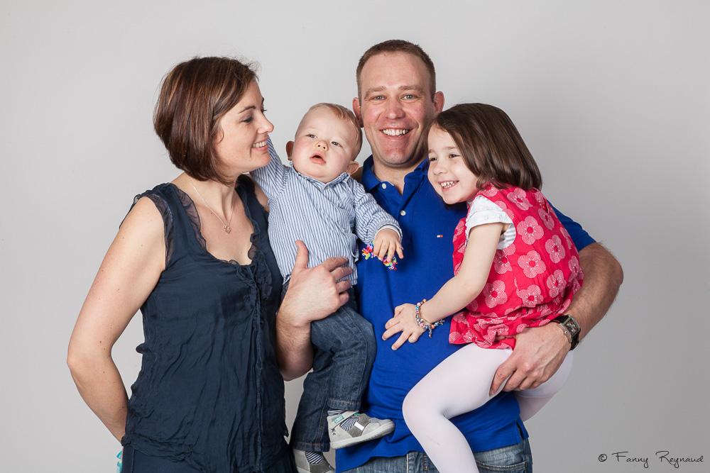 Photographie d'un couple et leurs deux jeunes enfants en studio, pendant une séance en studio en famille.