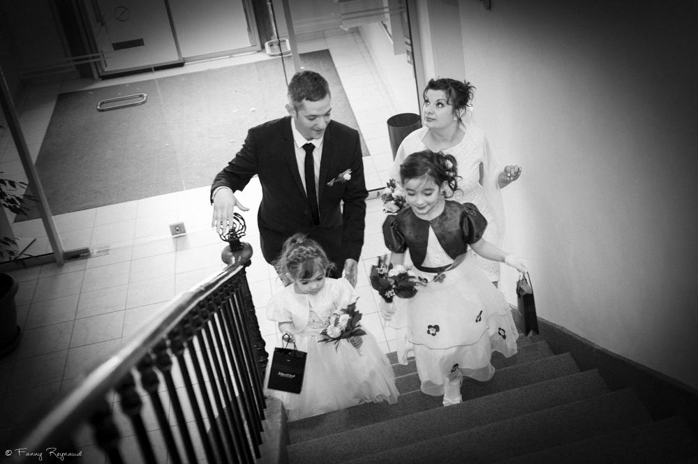 Arrivée des mariés à la mairie de vic-le-comte. Le couple monte l'escalier avec leurs deux petites filles. © Fanny Reynaud photographe de mariage professionnel en auvergne.