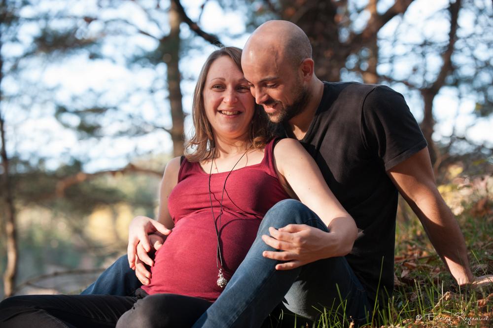 Moment complice en forêt d'un couple attendant en enfant. Shooting grossesse en extérieur par un photographe professionnel dans le puy-de-dome.