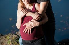 Photographie d'une femme enceinte avec son compagnon au lac de la cassière en auvergne, détails sur le ventre et les mains. Cadrage coupé au sourire de la future maman. Séance de photographie en extérieur par fanny reynaud photographe professionnelle à clermont-ferrand.
