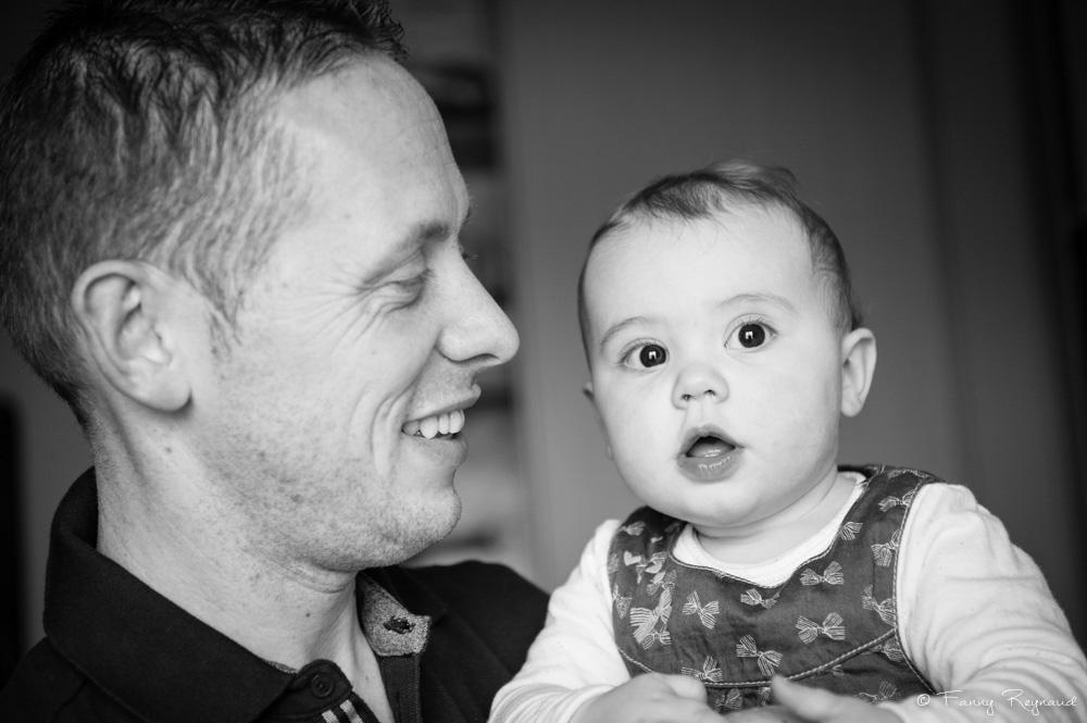 Photo d'une petite fille dans les bras de son papa, séance de portrait de famille à domicile dans les environs de clermont-ferrand par un photographe professionnel.