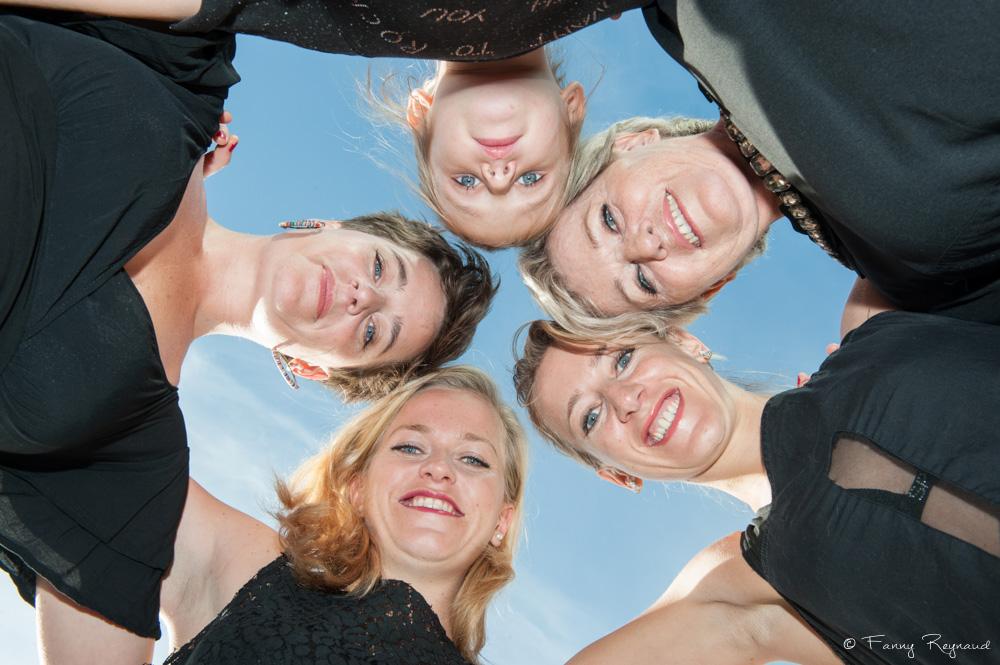 Photographie de soeurs et de leur mère en contre-plongée : elles forment un cercle sous le ciel bleu d'automne. Extrait d'une séance photo à domicile près de clermont-ferrand par un photographe professionnel.
