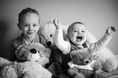 Photo de deux jeunes enfants souriant et jouant avec des peluches dans leur lit, extrait d'une séance à domicile dans les environs de riom, par une photographe professionnelle.