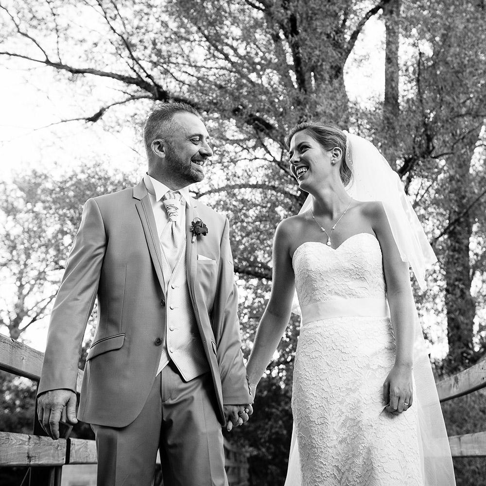 Photo de couple sur un pont sur la sioule à Pontgibaud près du domaine de la palle où les mariés ont organisé leur soirée. Photographie noir et blanc par un photographe professionnel de clermont-ferrand.