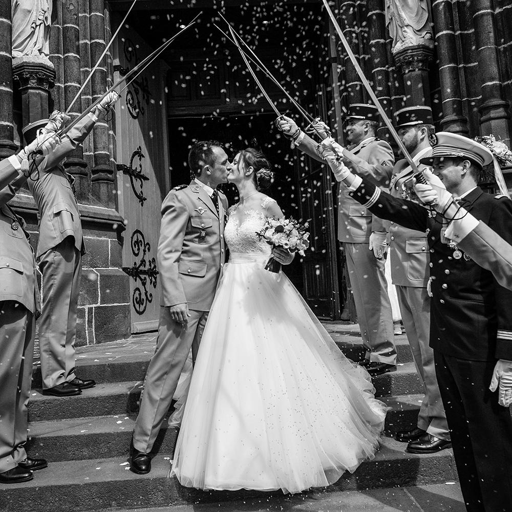 Sortie de l'église saint eutrope à clermont-ferrand d'un mariage de militaire avec une haie d'honneur de sabres.