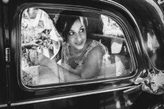 la mariee regarde par la fenetre avant de sortir d'une voiture de clermont, photographie professionnelle en noir et blanc à clermont ferrand
