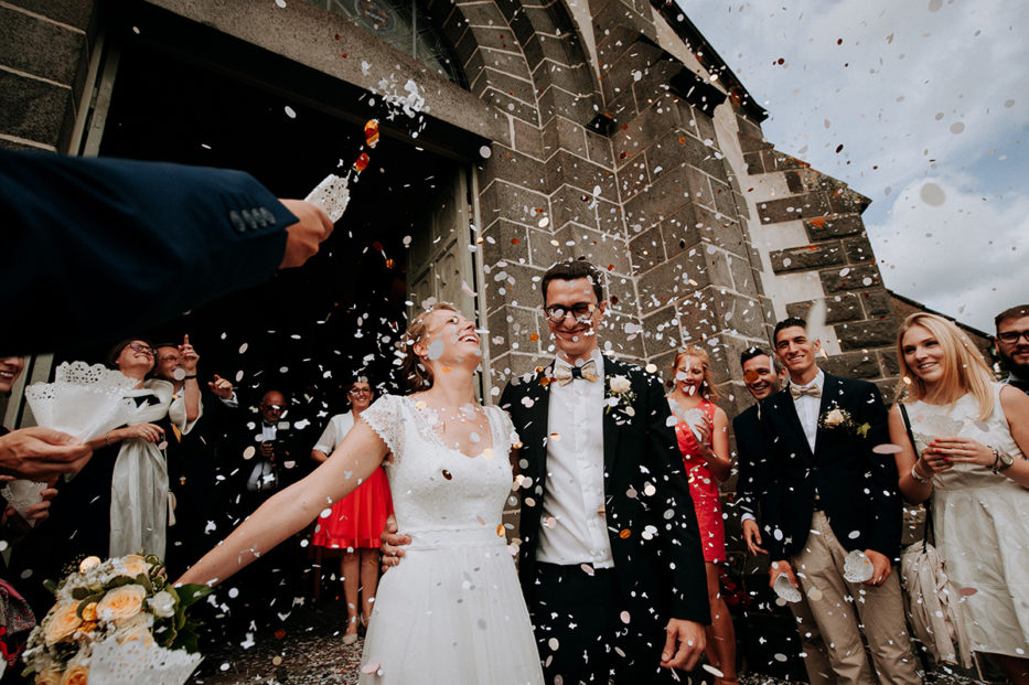 lancé de confettis à la sortie de l'église mariage en auvergne, photographe professionnel