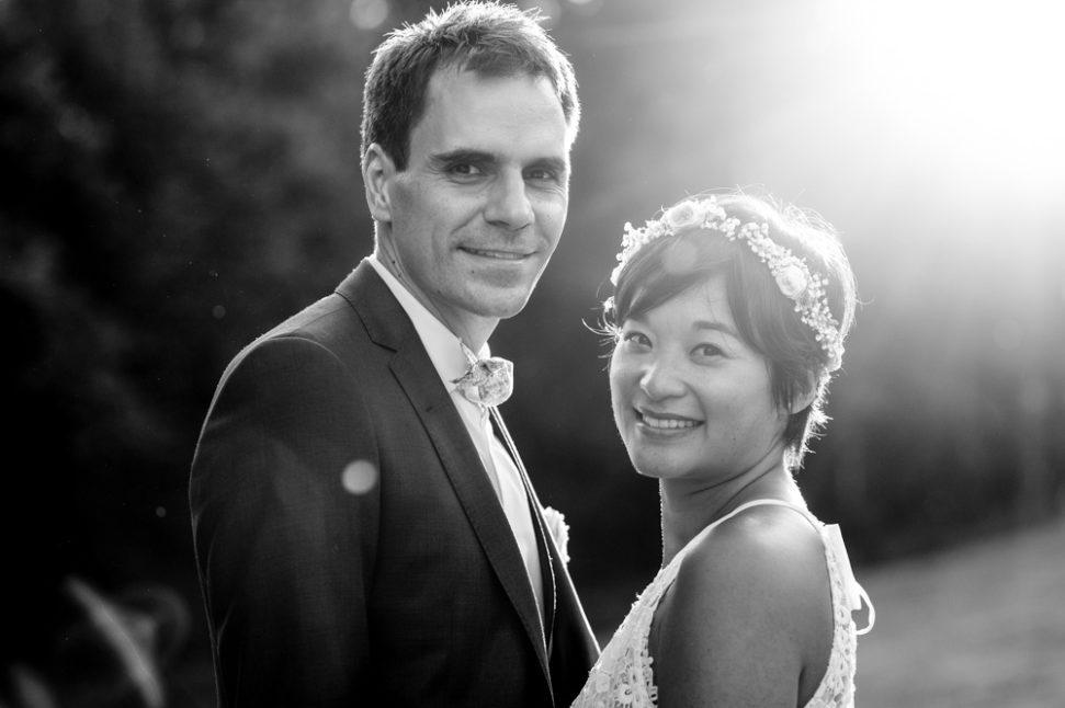 photographie en contre jour d'un couple de mariés lumière de fin de journée doree