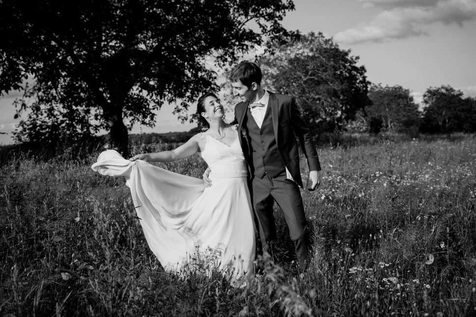 photo d'un couple de maries dans un champ de coquelicot pres du chateau de feligonde à sayat spontanee et fun