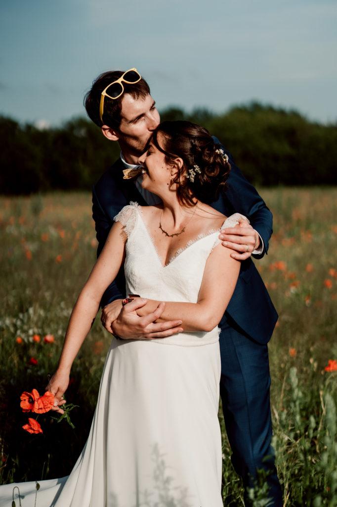 photographie d'un couple de mariés dans un champ de coquelicots en auvergne