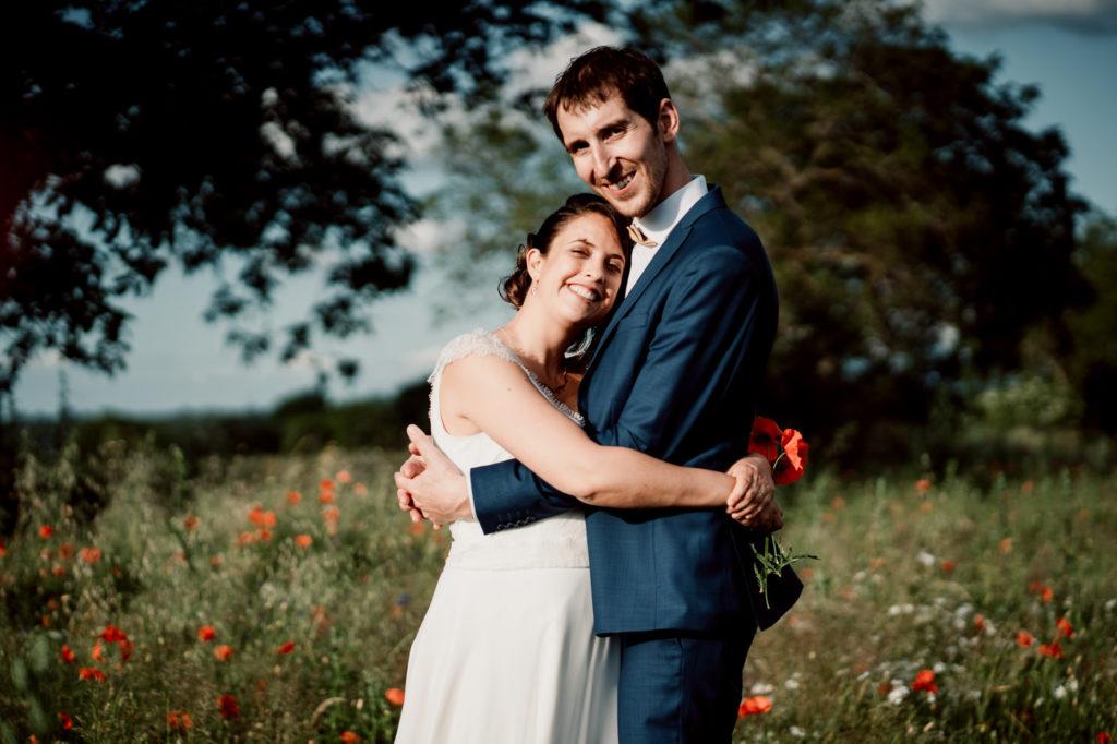photographie de mariés dans un champ de coquelicots près du chateau de feligonde a sayat